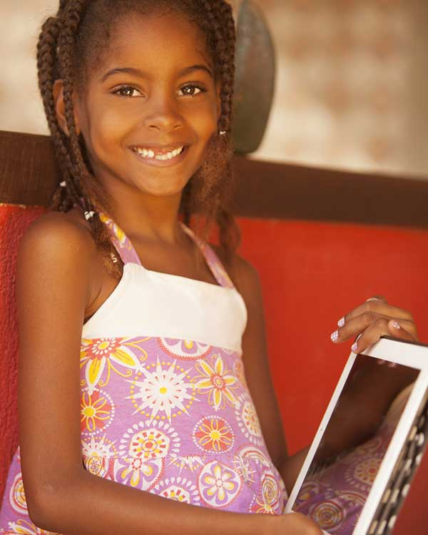 Young girl smiling holding a tablet
