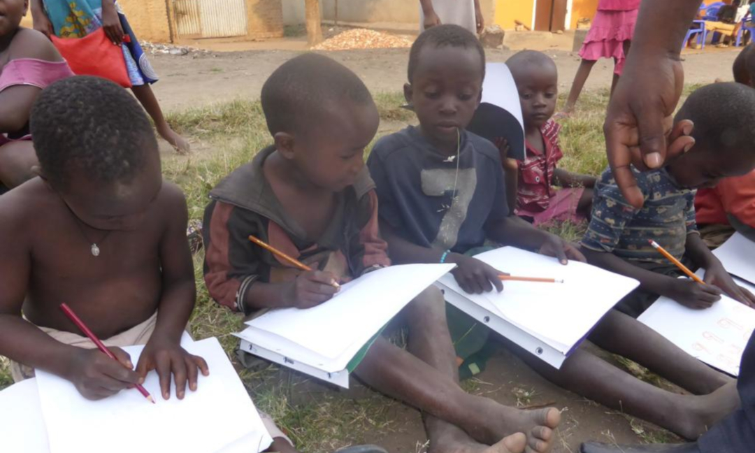 Children writing on paper at school